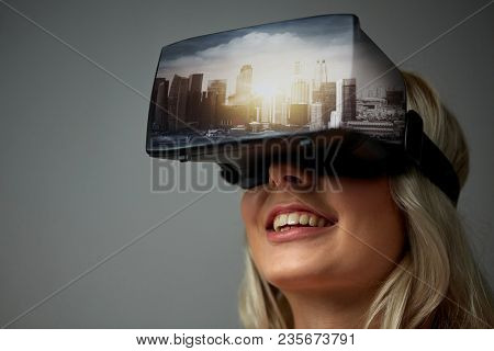 technology, augmented reality, entertainment and people concept - happy young woman with virtual headset or 3d glasses playing video game with singapore city on screen over gray background