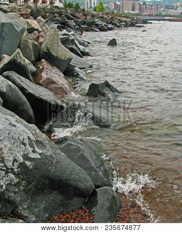 Waves Against Dark Stone Breakwater On Overcast Day In Duluth.