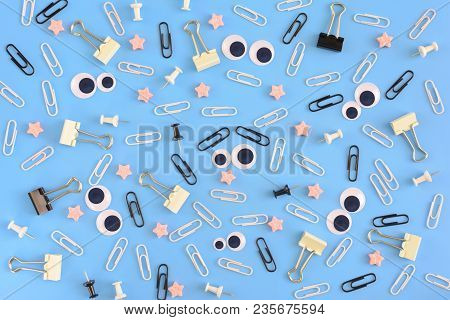 White Staples, Puppet Eyes And Pink Stars Are Randomly Scattered On A Blue Background. Funny Smiley