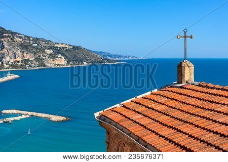 Church roof with cross overlooking Mediterranean sea and shoreline of Menton - small town on French Riviera.