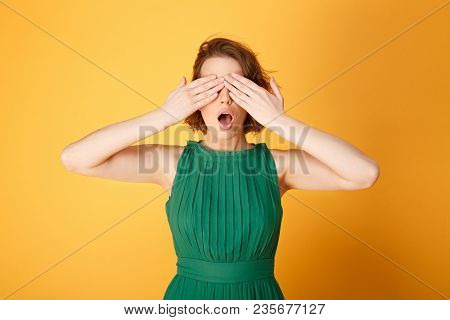 Obscured View Of Shocked Woman Covering Eyes With Hands Isolated On Orange