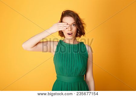 Obscured View Of Attractive Woman Covering One Eye With Hand Isolated On Orange
