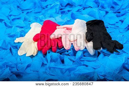 New Latex Medical Gloves On Background Of A Lot Of Blue Rubber Gloves Close Up