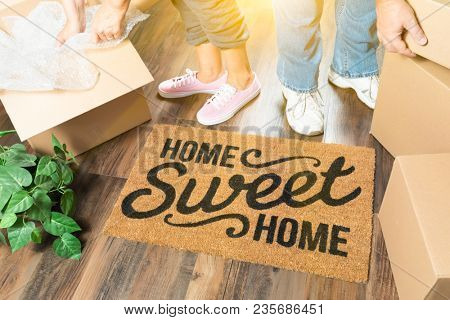 Man and Woman Unpacking Near Home Sweet Home Welcome Mat, Moving Boxes and Plant.