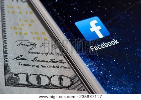 New York, Usa - April 11, 2018: Facebook Icon App On Smartphone Close-up On Dollar Currency Backgrou