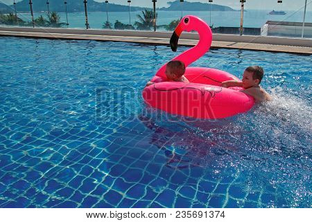 Children Play With An Inflatable Toy In The Outdoor Pool. Two Cute Boys Float On An Inflatable Pink