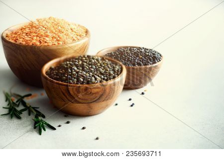 Assorted Lentils. Marble, Red And Black Raw Organic Lentils In Wooden Bowls With Rosemary On Grey Co