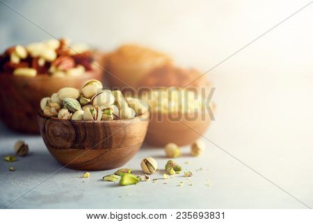 Pistachios Nuts In Wooden Bowl. Food Mix Background, Top View, Copy Space, Banner. Assortment Of Nut