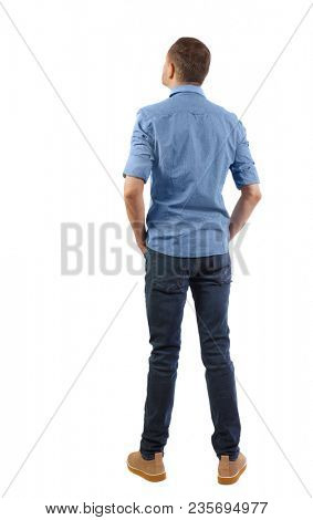 Back view of man in dark jeans. Standing young guy. Rear view people collection.  backside view of person.  Isolated over white background. A young man in a blue shirt with a short sleeve