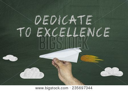 Paper Airplane And Text On Chalkboard: Dedicated To Excellence.