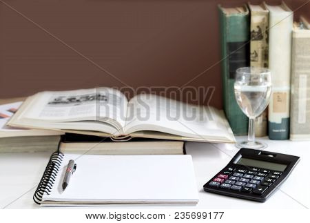 Open Hardback And Textbook Stacked With A Calculator On The Table. The Concept Of Intelligence Comes