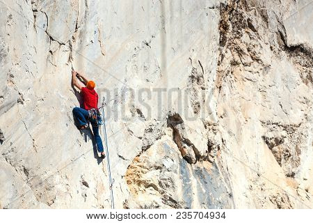 A Man Is Training To Climb On A Rock.