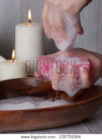 Washing Hands With Soap On A Background Of Burning Candles.