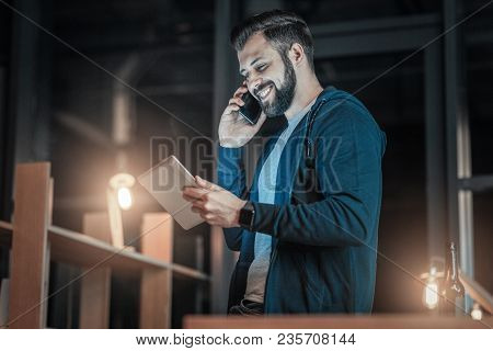 Business Talk. Low Angle Of Optimistic Vigorous It Guy Rising Tablet While Speaking On Phone And Lau