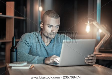Advanced Programming. Attentive Concentrated It Guy Using Laptop While Sitting At Table And Touching