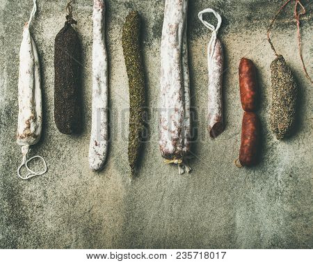 Variety Of Spanish Or Italian Cured Meat Sausages. Flat-lay Of Fuets And Salamies Over Rough Grey Co
