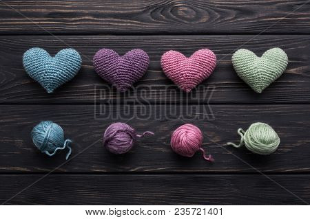 Colorful Handicraft Crocheted Hearts & Skeins Of Yarn On Old Gray Wooden Table. Retro Color Palette.