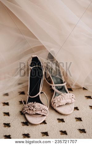 Pink Elegant Shoes Of The Bride's Sandals On The Floor Next To The Wedding Dress. Wedding Preparatio