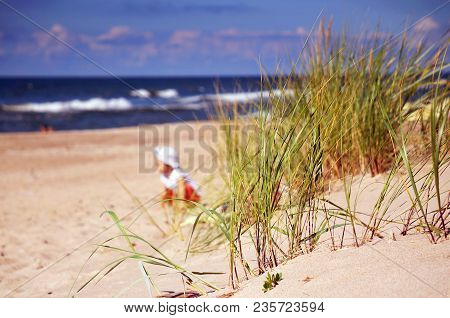 Happy Free Little Boy Running Across Field Of Dried Grass On Sea Background In Summer