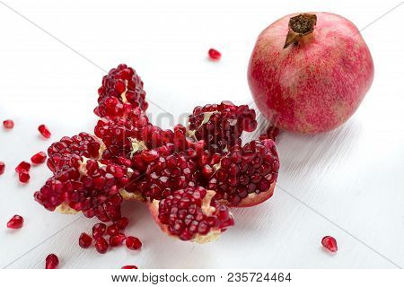 Cut-up dissected tasty garnet fruit pomegranate with rolled out seeds isolated on white background poster