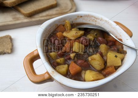 Appetizing Beautiful Soup With Potatoes, Onions, Carrots And Beans. On A Light Background And Close-