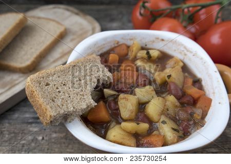Appetizing Beautiful Soup With Potatoes, Onions, Carrots And Beans. On An Old Wooden Background And