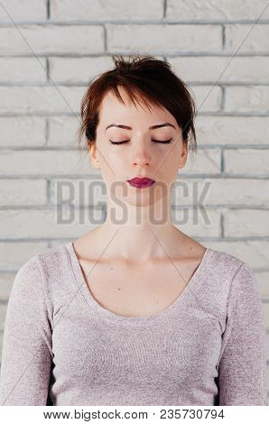 A pretty girl with eyes closed as in meditation, peaceful look, with white brick wall in the background. Face mimic for fitness exercise poster