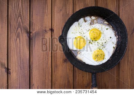 Appetizing Fried Eggs In An Old Frying Pan