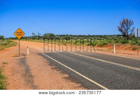 Yellow Sign Gravel Road. Caution The End Of A Good Road. Ended Asphalt, The Beginning Of Off Road Te