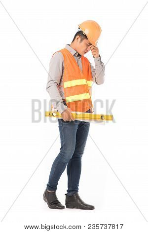 Studio Portrait Of Construction Worker In Orange Waistcoat And Hardhat Holding Levelling Tool And Bu