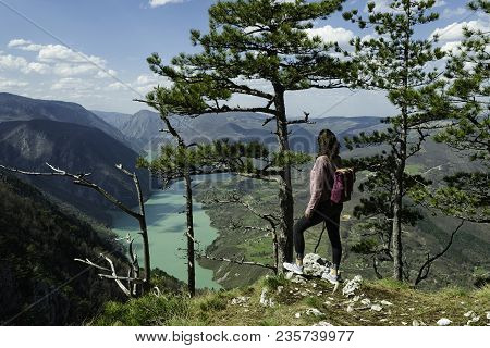 Traveler on a beautiful mountain view. Traveler on mountain rock enjoying beautiful mountain view.  Girl traveler standing on a rock. Travel. Traveler. Vacation. Hipster travel backpacking.