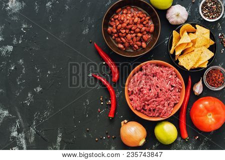 Ingredients For Mexican Dishes Chili Con Carne. Black Concrete Background, Top View, Space For Text