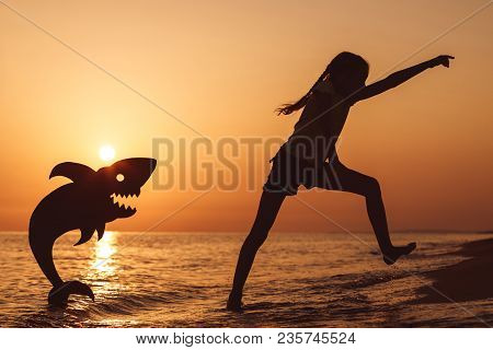 One Happy Little Girl Playing On The Beach At The Sunset Time.
