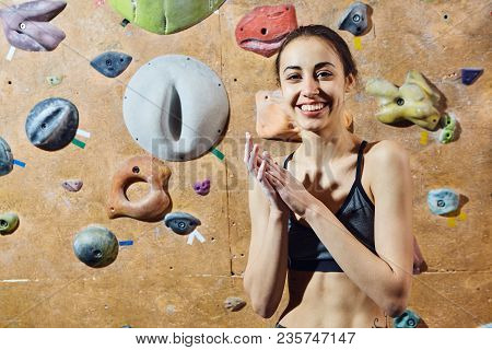 Woman Climber Preparing To Climb Indoors In Bouldering Gym With Dramatic Light. Woman Using Chalk