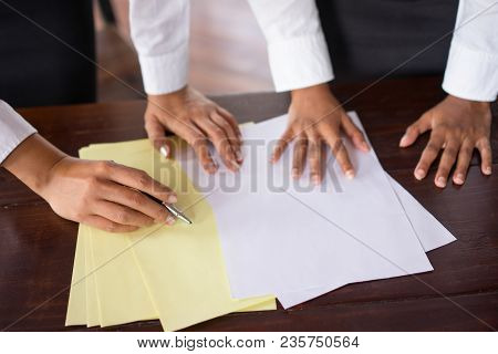Closeup Of Two Female Coworkers Working With Documents At Table. Women Are Unrecognizable. Paperwork