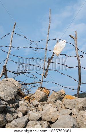 Rusty Barbed Wire And Wooden Pole Of A Fence Near Cres