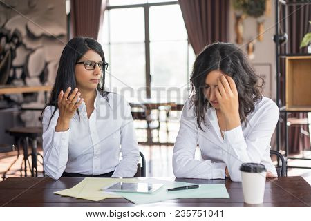Serious Business Woman Accusing Colleague Of Making Mistake. They Are Sitting At Table In Cafe. Diff