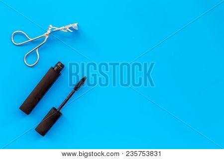 Basic Products For Eyelashes Makeup. Mascara And Eyelash Curler On Blue Background Top View.