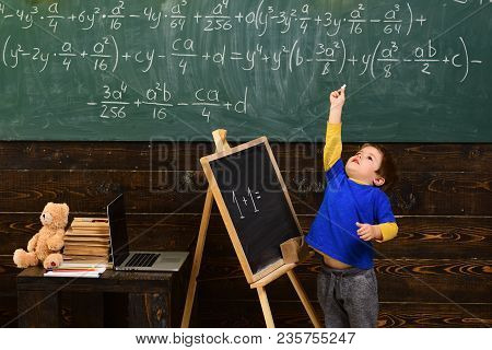 Tiptoeing Boy Pointing Up With Chalk In Classroom. Small Kid Learning Math. Early Development Concep
