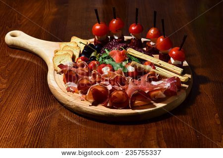 Board With Snacks On Wooden Table. Restaurant Dish Concept. Cold Appetizers With Tomatoes, Sausage,