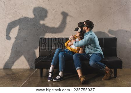 Shadow Of Man Holding Knife And Scared Couple In Virtual Reality Headset On Couch