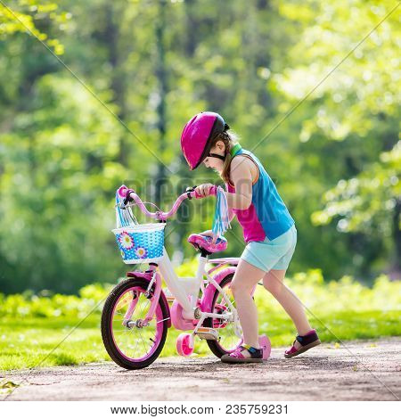 Child Riding Bike. Kid On Bicycle In Sunny Park. Little Girl Enjoying Bike Ride On Her Way To School
