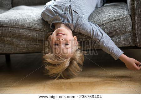 Cute Funny Boy Lying Upside Down On Sofa Looking At Camera, Smiling Playful Preschool Child Having F