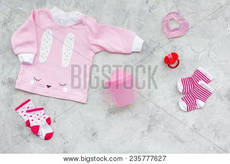 Newborn Baby's Background. Clothes For Small Girl With Booties On Grey Background Top View