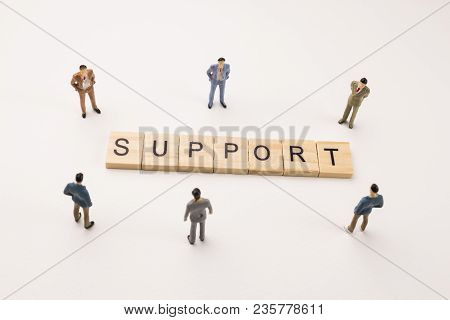 Miniature Figures Businessman : Meeting On Support Word By Wooden Block Word On White Paper Backgrou