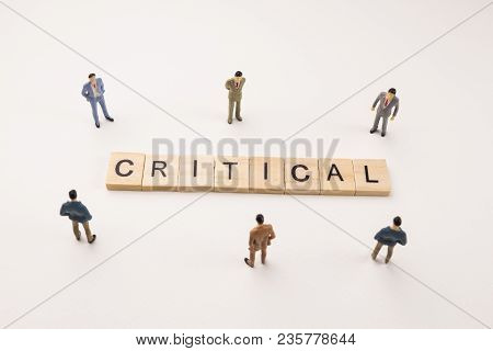 Miniature Figures Businessman : Meeting On Critical  Word By Wooden Block Word On White Paper Backgr