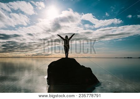 Rear View Of A Young Happy Woman Enjoying Journey, Looking Up And Holding Her Hands In The Air. Icel