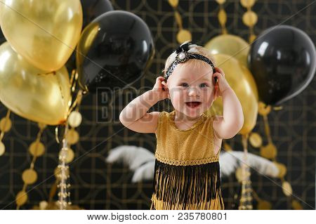 Baby Girl Birthday Party Decorated With Black And Golden Balloon. Horizontal Portrait.