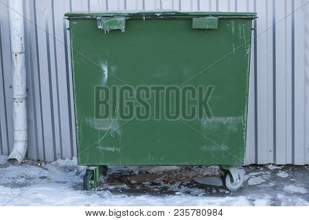 Green Garbage Bin. Municipal Garbage Dump. Against A Gray Background