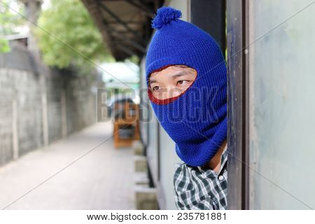 Masked Burglar Wearing A Balaclava Sneaking Behind A Pole Before The Burglary. Crime Concept